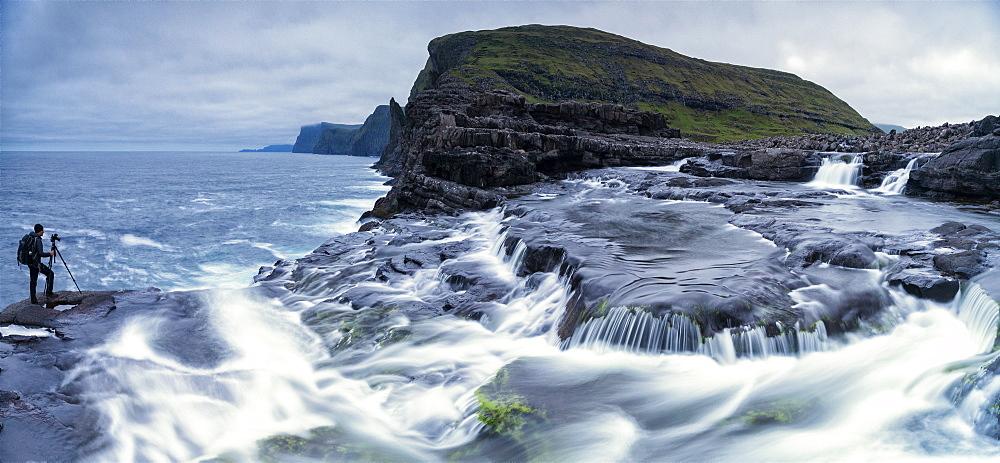 Panoramic of photographer at Bosdalafossur waterfall, Vagar island, Faroe Islands, Denmark, Europe