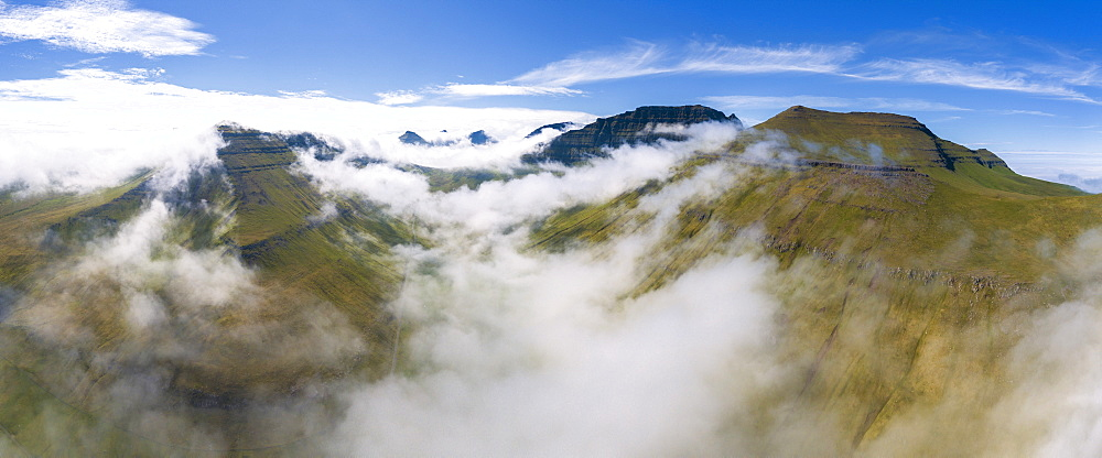 Panoramic aerial view of clouds on mountain peaks, Gjogv, Eysturoy island, Faroe Islands, Denmark