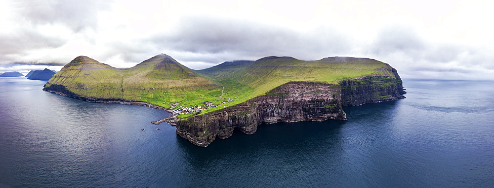Panoramic aerial view of cliffs and village of Gjogv, Eysturoy island, Faroe Islands, Denmark (drone)
