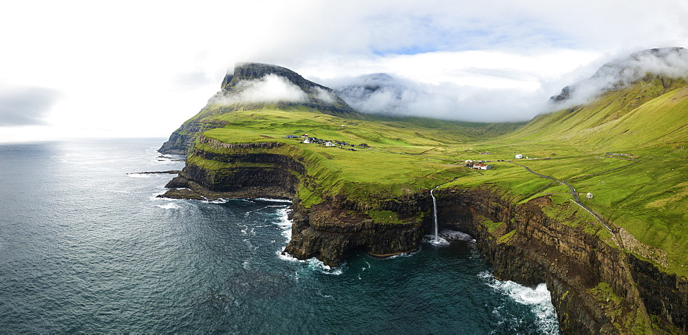 Aerial panoramic of waterfall and cliffs, Gasadalur, Vagar island, Faroe Islands, Denmark (drone)