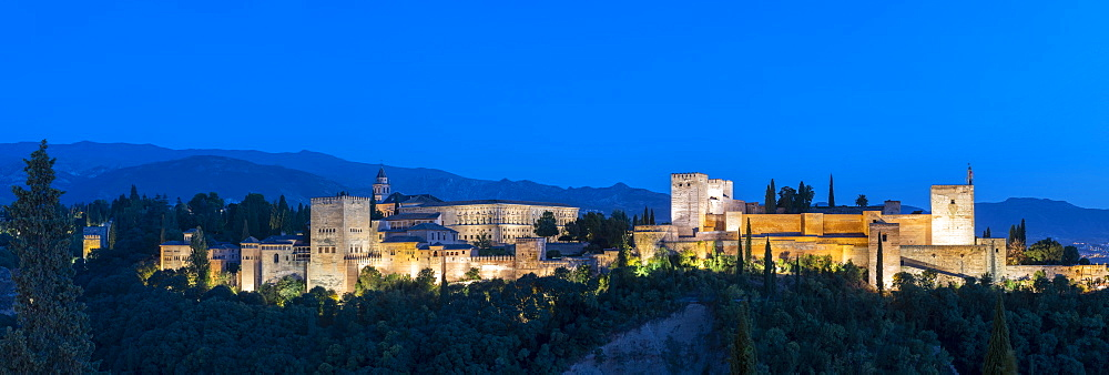 Panoramic of the illuminated Alhambra palace and fortress at dusk, Granada, Andalusia, Spain