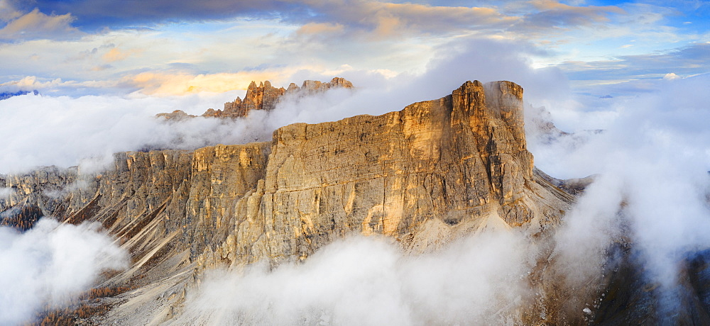 Aerial view by drone of sunset over Lastoi De Formin and Cima Ambrizzola in a sea of clouds in autumn, Giau Pass, Dolomites, Veneto, Italy, Europe