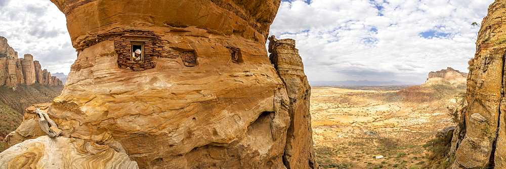 Aerial panoramic of priest looking out from Abuna Yemata Guh rock-hewn church, Gheralta Mountains,Tigray region, Ethiopia (drone