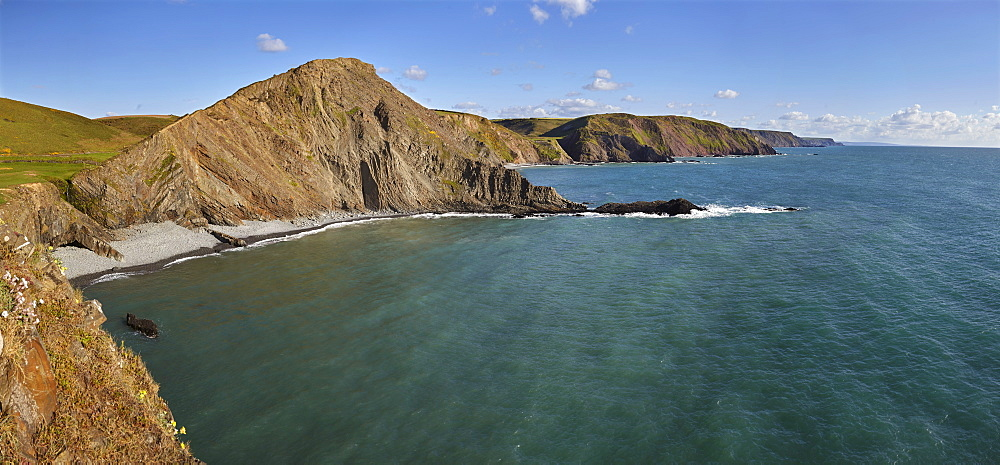 Rugged cliffs along southwest England's Atlantic coast, seen in calm summer weather, near Hartland Quay, in Devon