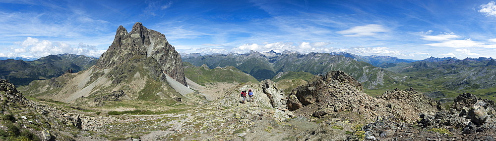 Walkers descend from the top of Pic Peyreget while hiking the GR10 trekking trail in France