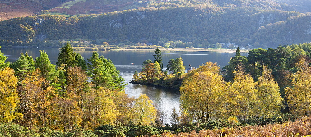 Autumn colours and sunshine over Brandlehow and Manesty wood, Lake Derwent Water, Lake District, England.