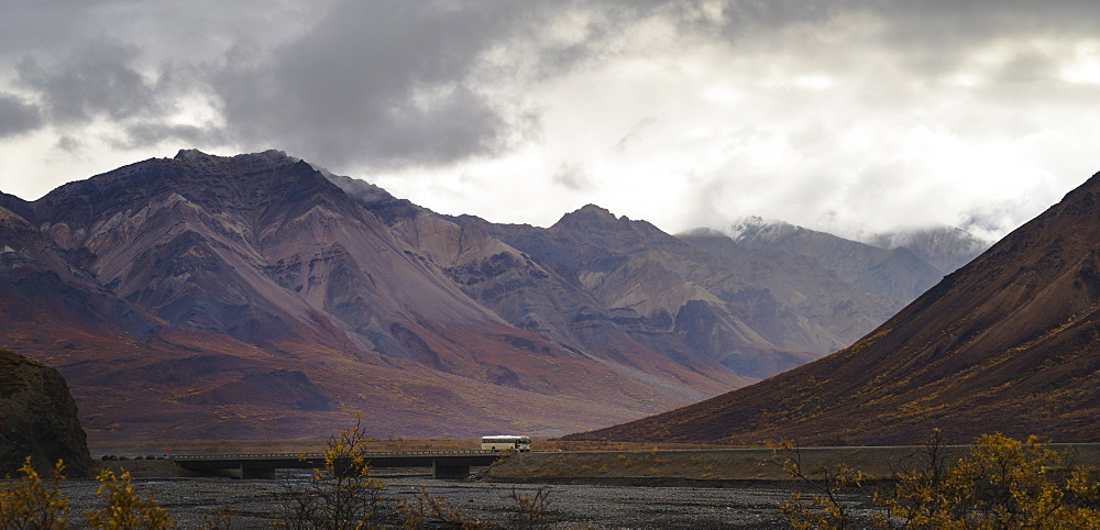 Tourist bus driving among mountains in the Denali National Park, Alaska, United States of America, North America