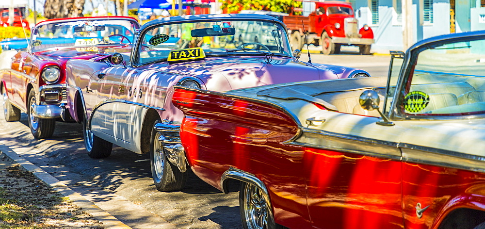 A row of classic American cars used as taxis in Varadero, Cuba, West Indies, Caribbean, Central America