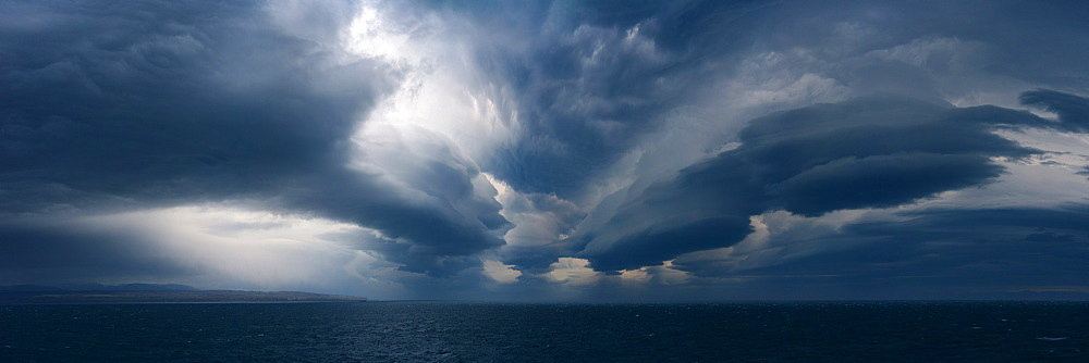 Panorama image of Lenticular clouds over the ocean