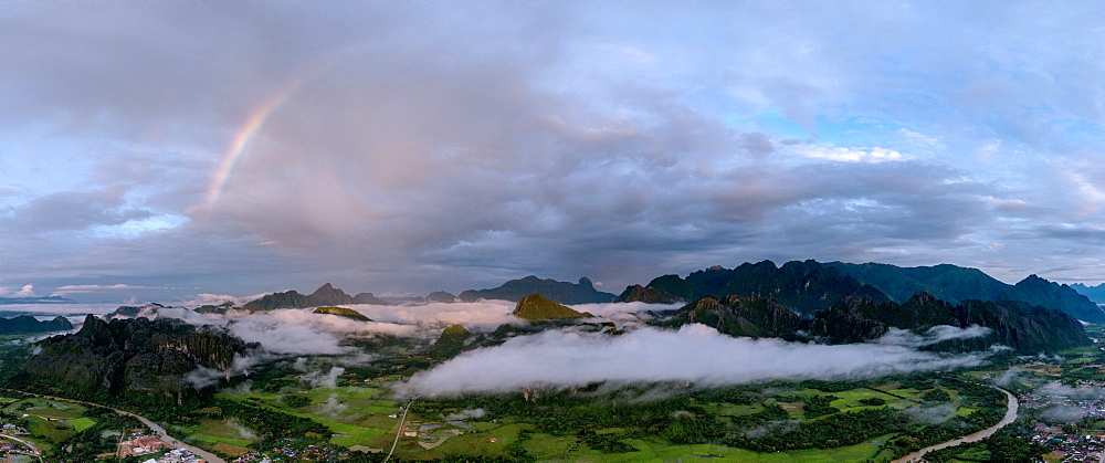 A panorama of a rainbow as dawn breaks over the mountains of Vang Vieng