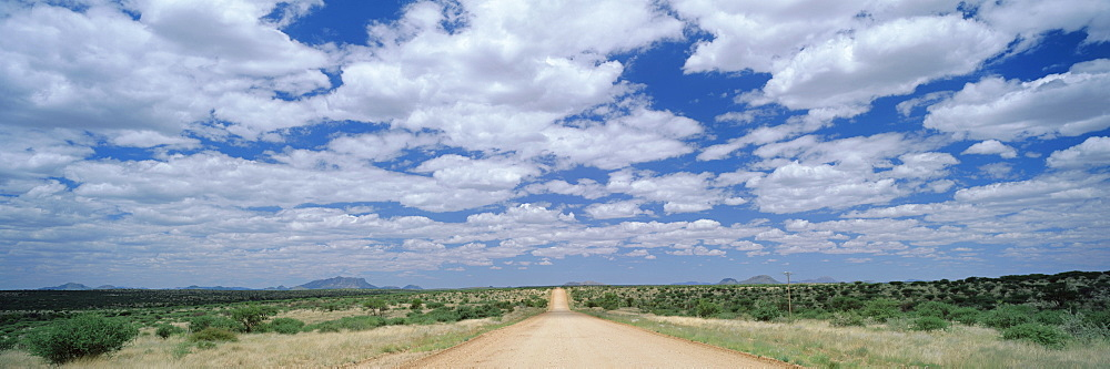 Straight gravel road cutting across grassy plain near Windhoek, Namibia