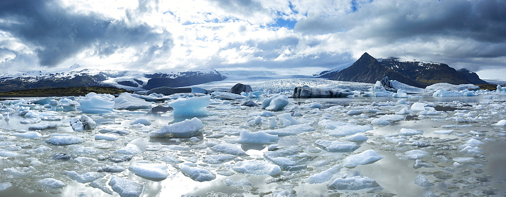 Panoramic view of Fjallsarlon, a glacial lake fed by Fjallsjokull at the south end of the Vatnajokull icecap showing icebergs floating on the surface of the lake, near Jokulsarlon, South Iceland, Iceland, Polar Regions
