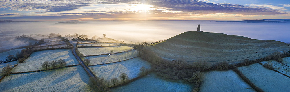 Aerial view by drone of frosty winter sunrise over Glastonbury Tor, Somerset, England, United Kingdom, Europe