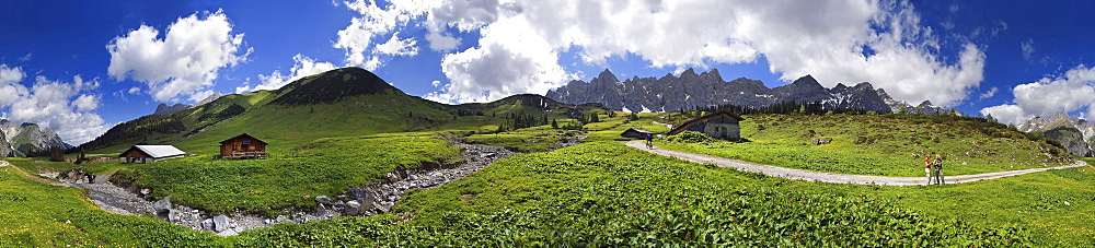 Panorama at the Ladizalm alipine pasture with Lalidererwaende Cliffs, hikers, meadows and clouds in the Karwendel Range, Tyrol, Austria, Europe