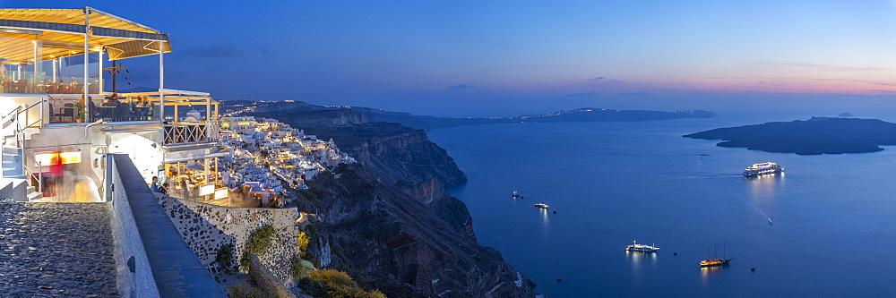 View of Greek restaurant overlooking the Mediterranean Sea at Fira at dusk, Firostefani, Santorini (Thira), Cyclades Islands, Greek Islands, Greece, Europe
