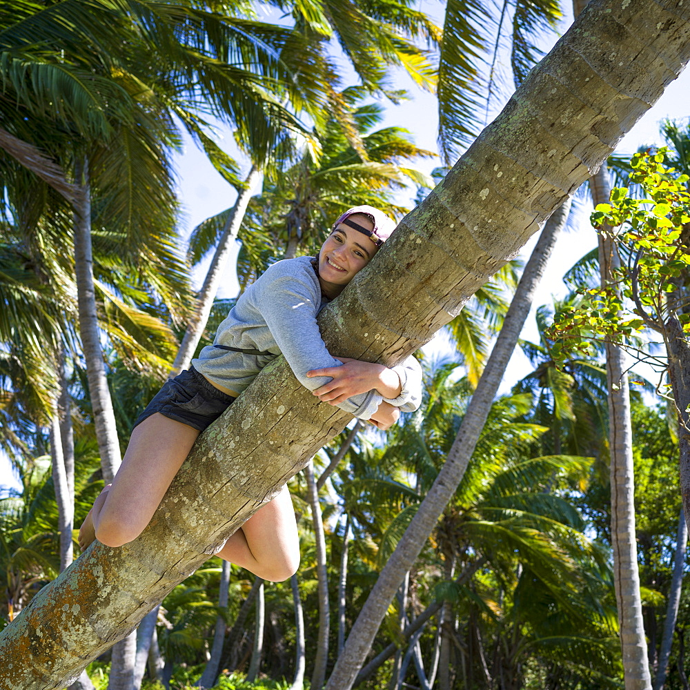 A teenage girl clings to a leaning tree trunk, Belize