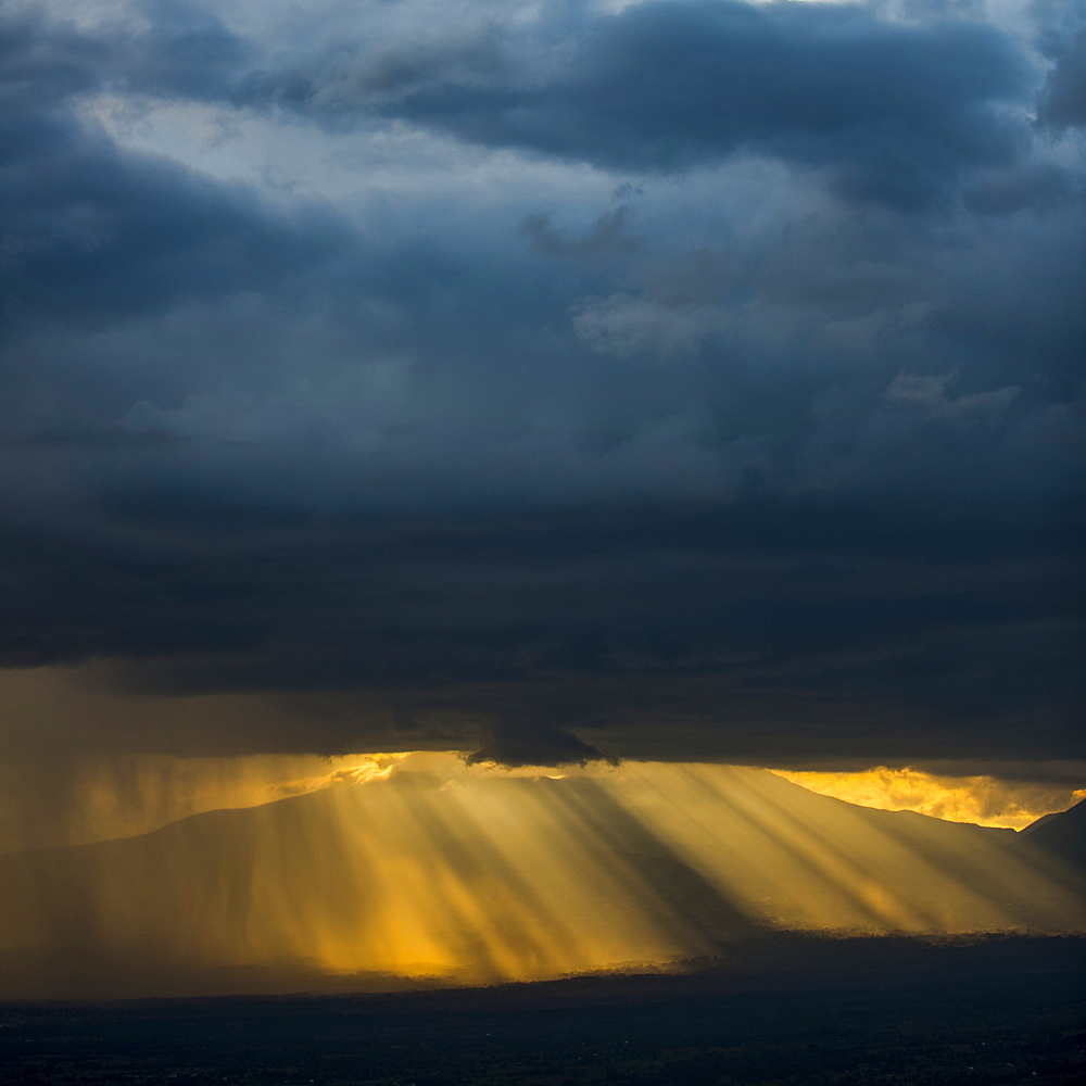 Golden sun rays and illuminated rainfall shining through the dark, ominous clouds with mountains in the distance, Volcanoes National Park, Northern Province, Rwanda
