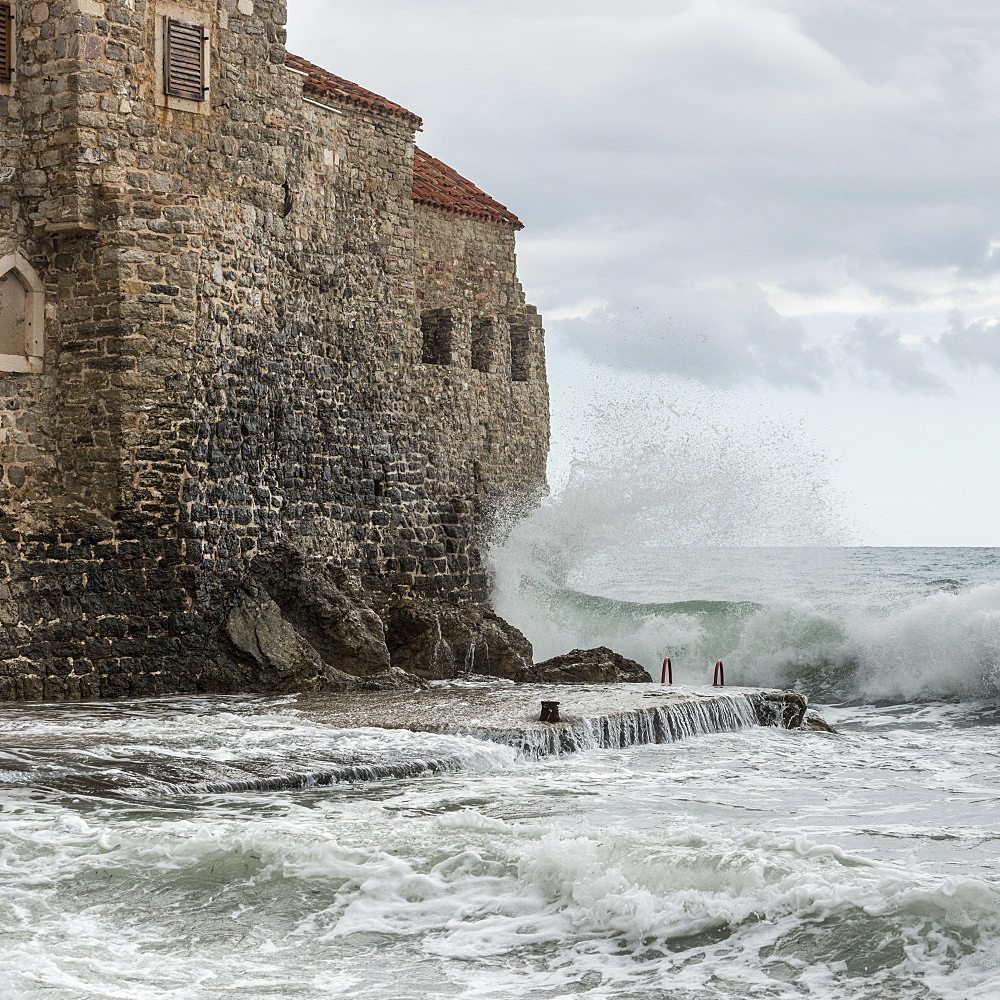 Waves crashing and splashing against the old stone walls along the coast of Budva, Budva, Opstina Budva, Montenegro