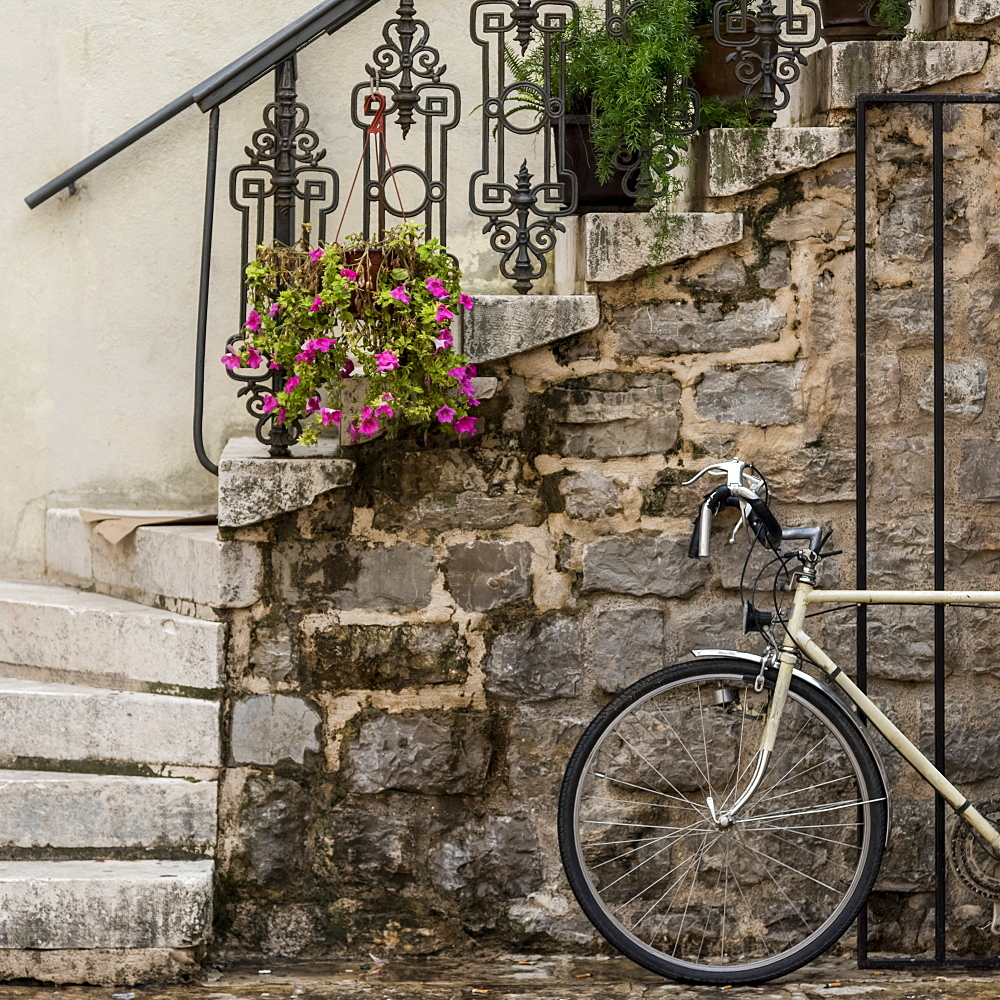 A bicycle parked beside a stone wall with steps leading up and plants decorating the railing, Budva, Opstina Budva, Montenegro