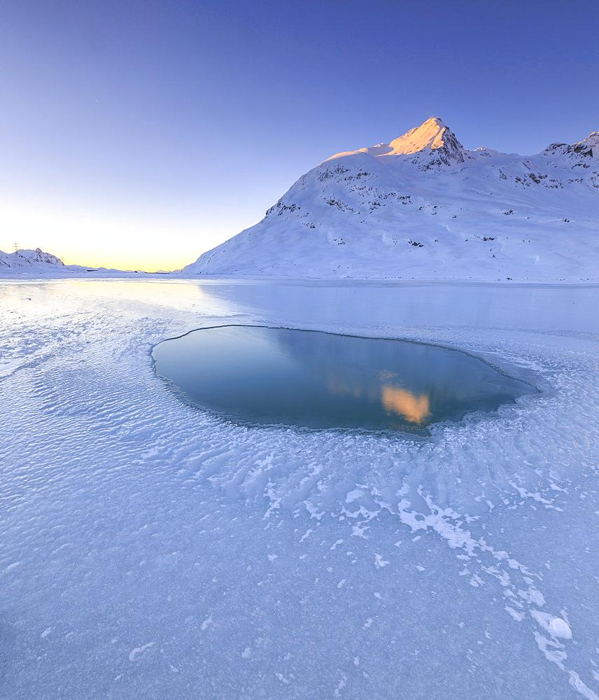 The sun illuminating a peak surrounding the frozen Lago Bianco by Bernina, reflecting in a pool in the center of the lake, Bernina Pass, Graubunden, Swiss Alps, Switzerland, Europe