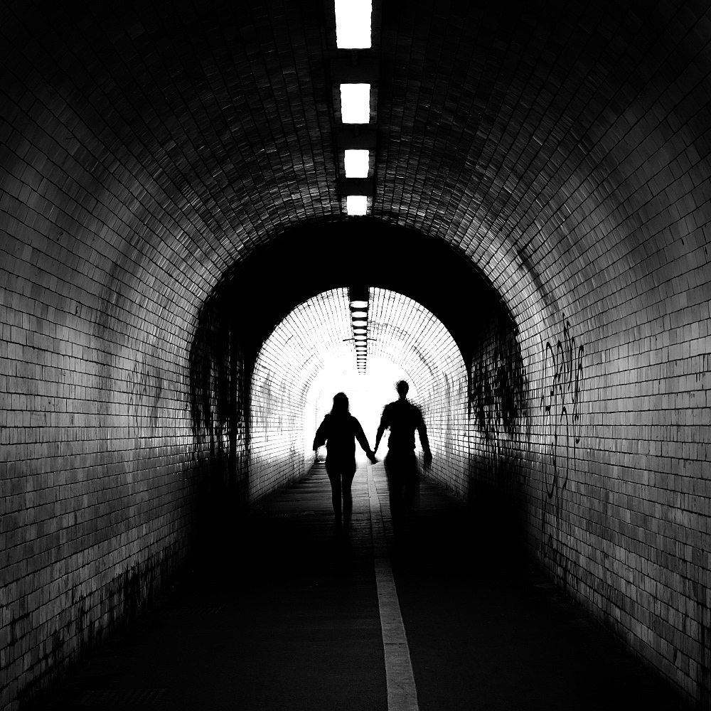 Couple walking into the light, York tunnel, York, England, United Kingdom, Europe - 1216-514