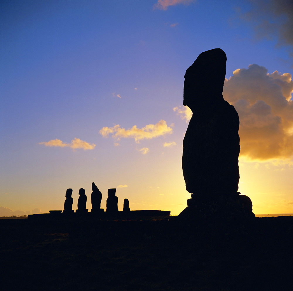 Silhouette of Ahu Tahai in foreground and behind the five moai (statues) of Ahu Vai Uri, Easter Island, Chile