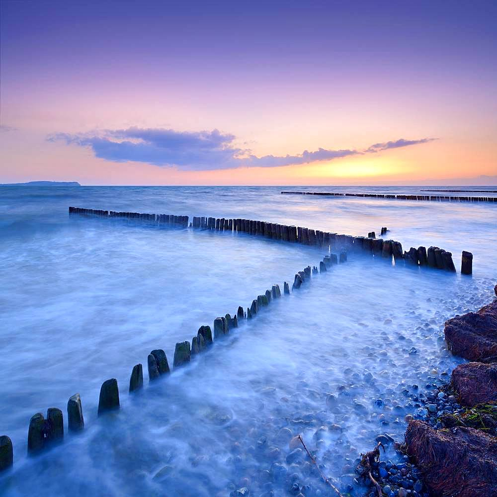 Sunset at the beach of the Baltic Sea, crossing groynes, on the horizon Hiddensee, island Ruegen, Mecklenburg-Western Pomerania, Germany, Europe