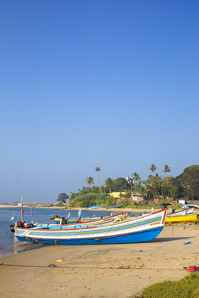 Fishing boats on beach with Tangasseri Lighthouse in background, Kollam, Kerala, India, Asia