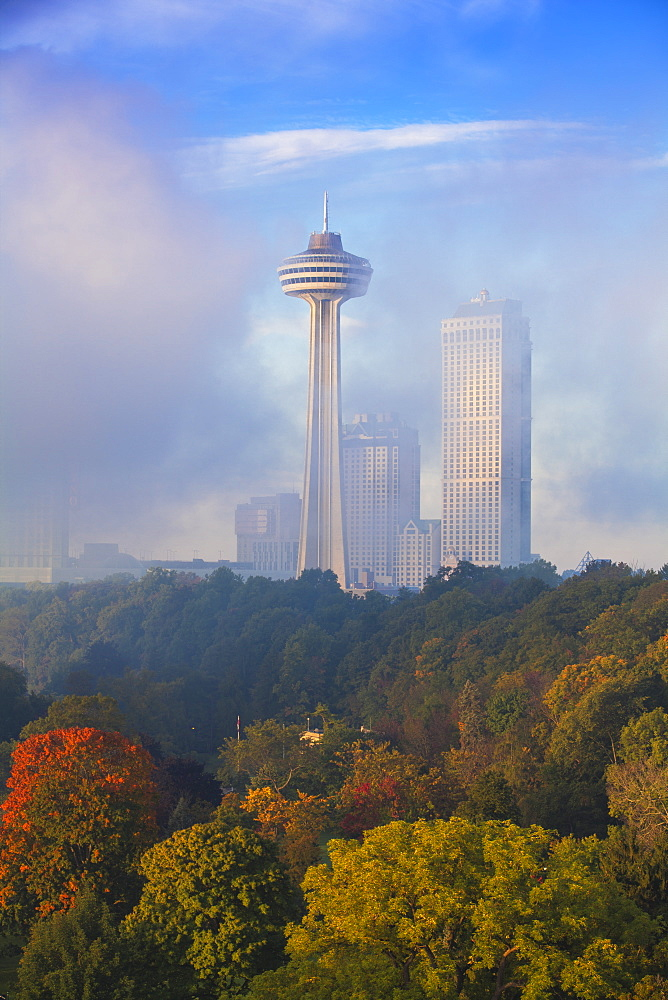 Mist from Horseshoe Falls swirling in front of Skylon Tower at dawn, Niagara Falls, Niagara, Ontario, Canada, North America
