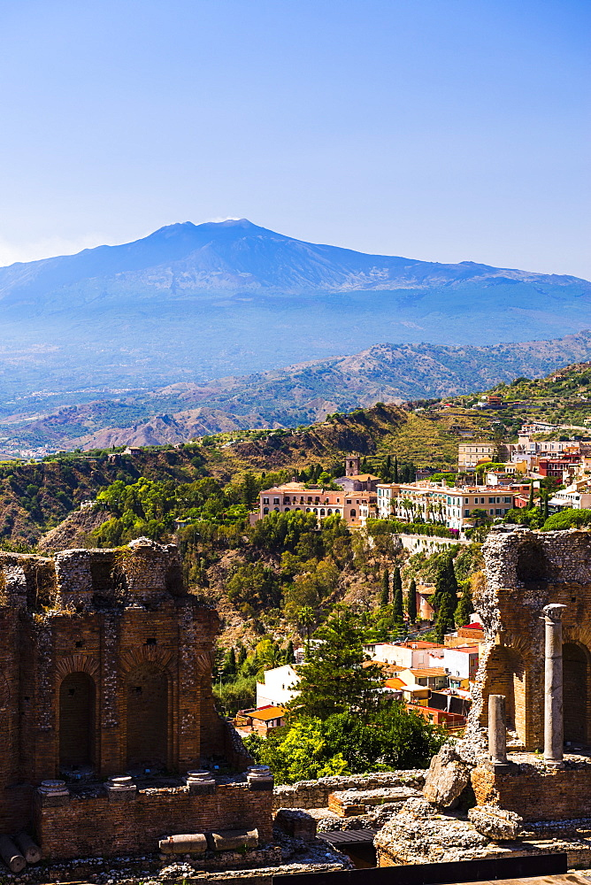 Mount Etna Volcano with ruins of Teatro Greco (Ancient Theatre) of Taormina in the foreground, Sicily, Italy, Europe