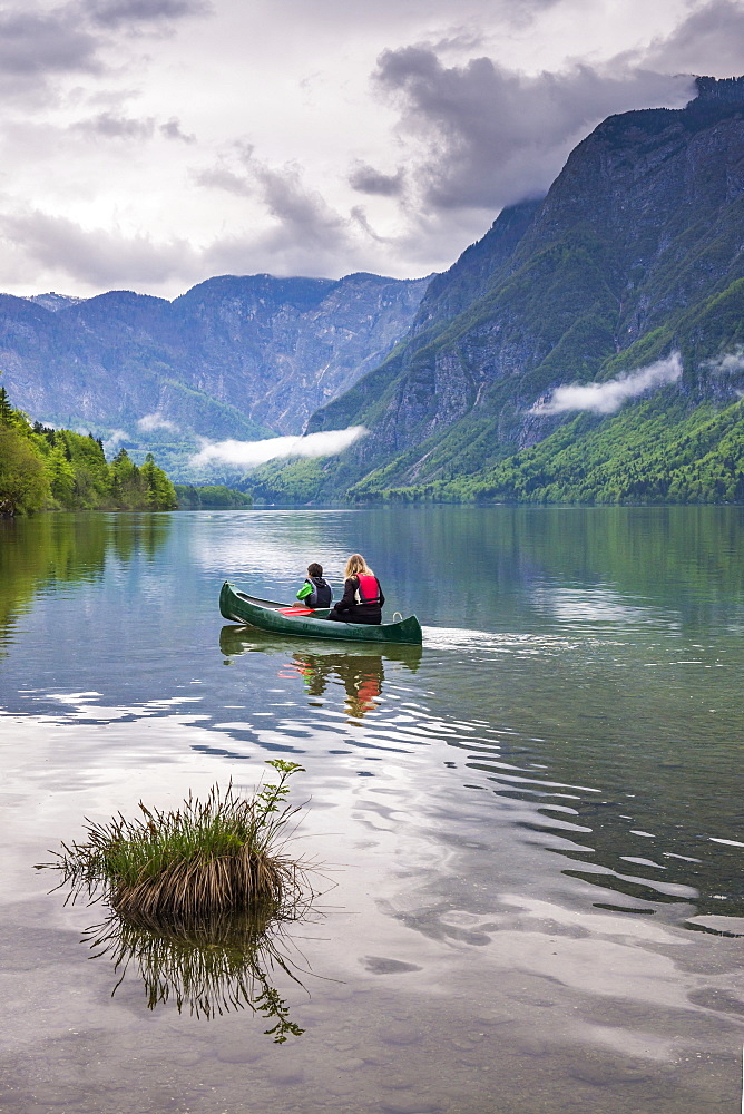 Mother and son canoeing on Lake Bohinj, Triglav National Park, Julian Alps, Slovenia, Europe