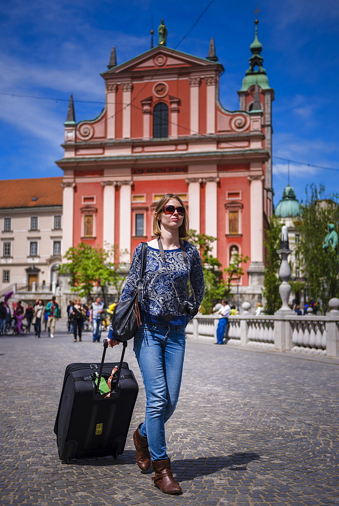 Tourist with suitcase, walking past the Franciscan Church of the Annunciation in Preseren Square, Ljubljana, Slovenia, Europe