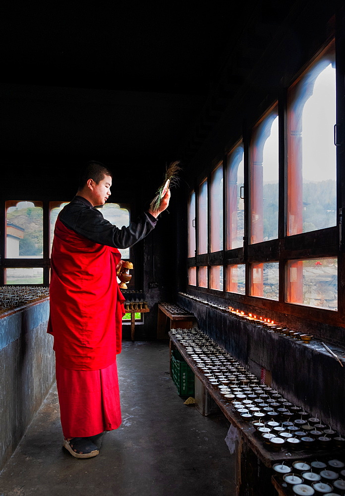 Portrait, Bhutanese Buddhist monk lights candles for worshippers to pray, Tamzhing Monastery, Bumthang District, Bhutan, Asia