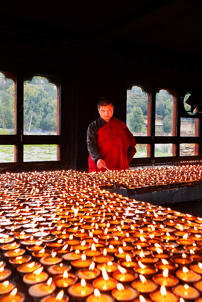 Portrait, Bhutanese Buddhist monk lights candles for worshipers to pray, Tamzhing Monastery, Bumthang District.