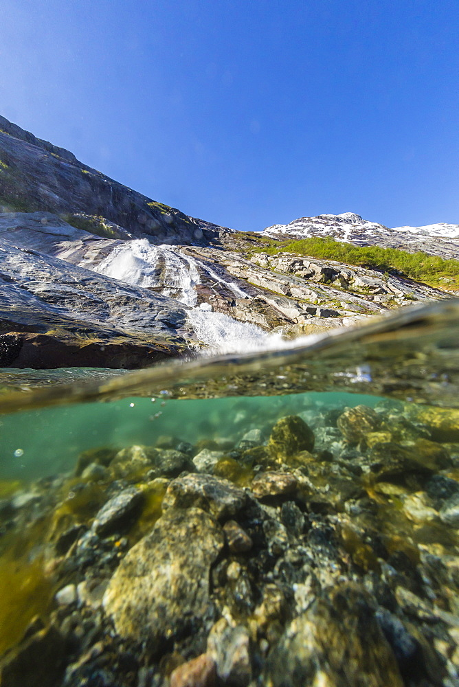 Above and below view of ice melt waterfall cascading down in Svartisen National Park, Melfjord, Nordfjord, Norway, Scandinavia, Europe