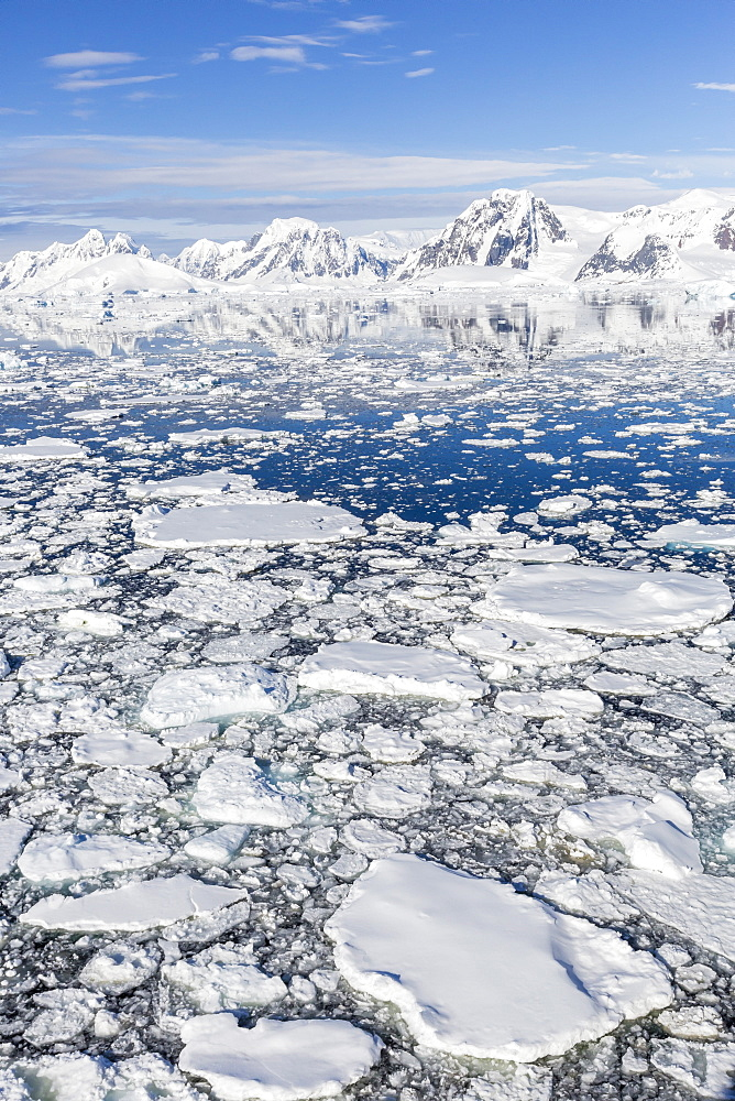 Snow-covered mountains line the ice floes in Penola Strait, Antarctica, Polar Regions