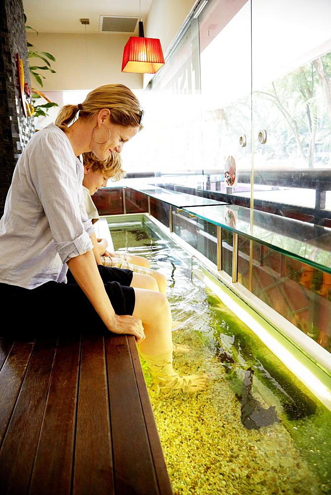 Woman and boy enjoying fish spa, Downtown Core, Singapore - 1113-104405