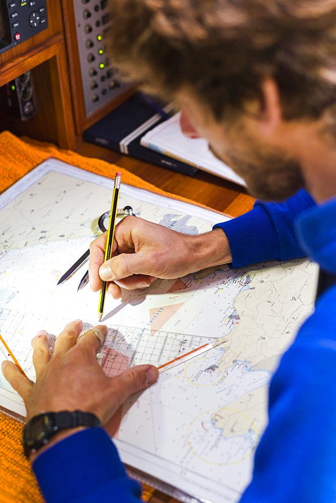 Skipper planing a route on a nautical chart at a sailing boat, Pula, Istria, Croatia - 1113-104459