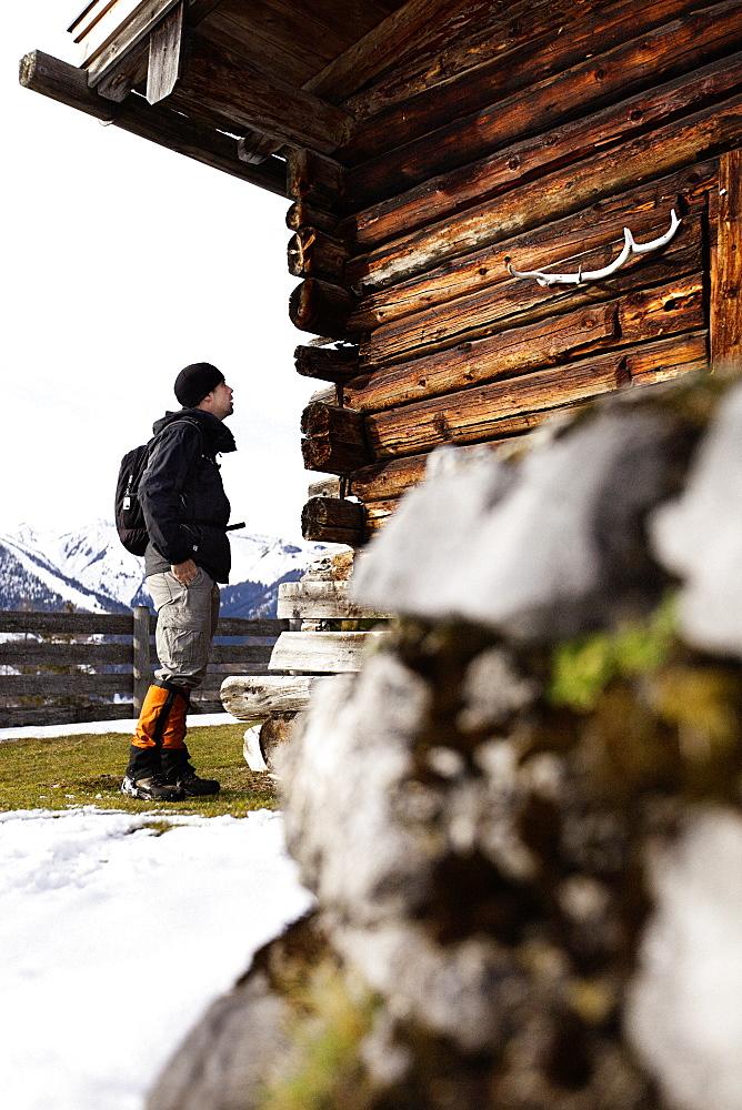 Hiker and wooden alpine hut, descent from Unnutz Mountain (2078 m), Rofan Mountains, Tyrol, Austria - 1113-104616