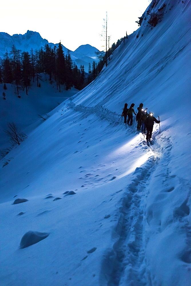 Backcountry skiers with headlamps at dawn, Tennengebirge mountains, Salzburg, Austria - 1113-104869