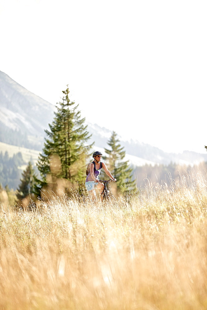 Young woman riding her bike near a meadow on a sunny day, Tannheimer Tal, Tyrol, Austria - 1113-104954