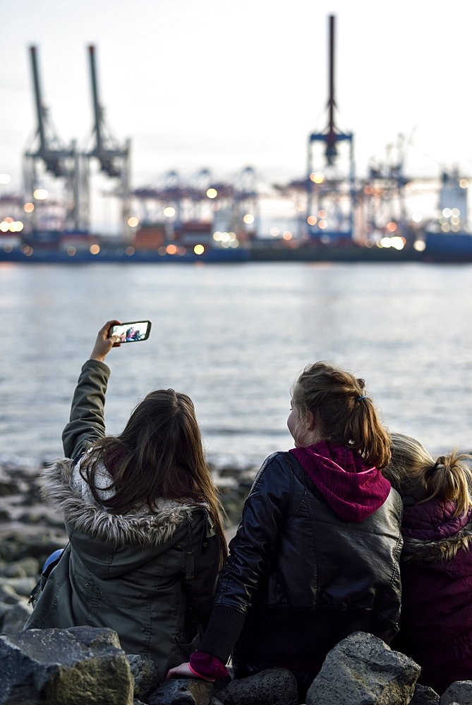 3 girls making selfie pictures at the Elbe River beach, Oevelgoenne, Hamburg, Germany, Europe - 1113-105007