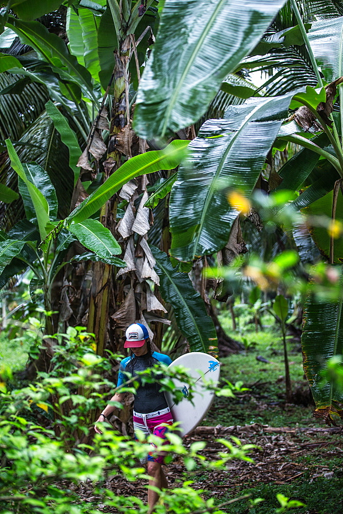 Young female surfer walking through a thick jungle, Sao Tome, Sao Tome and Principe, Africa - 1113-105188