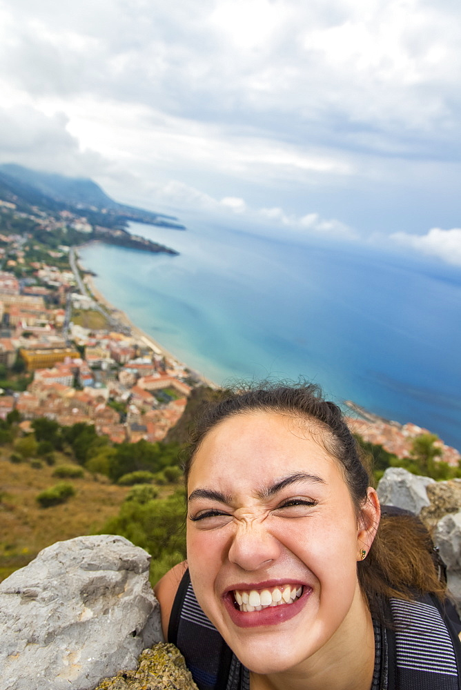 A young female tourist stands on a lookout above the Mediterranean coast, Cefalu, Sicily, Italy