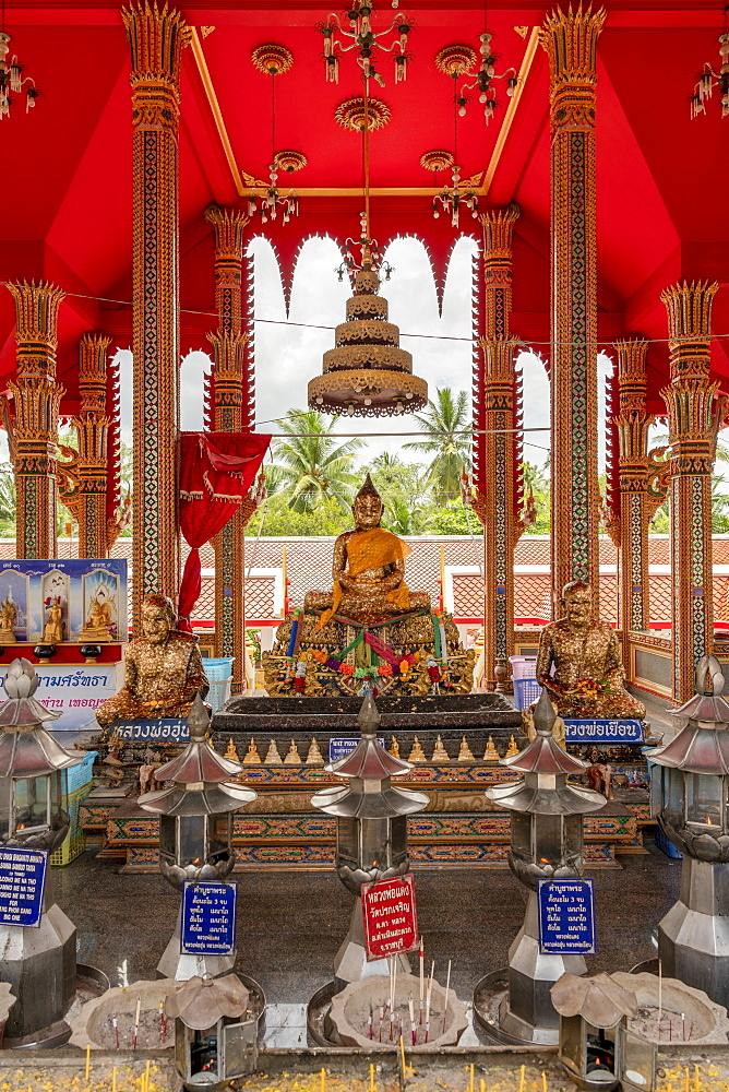 Three Buddha statues and offerings in temple, Otop Temple, Bangkok, Thailand