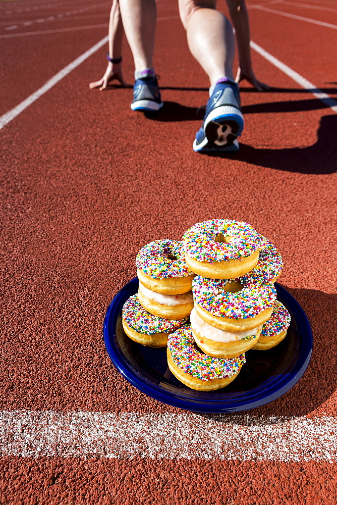 A plate full of candy covered donuts on a running track with a female runner in a lane in a starter stance, Calgary, Alberta, Canada