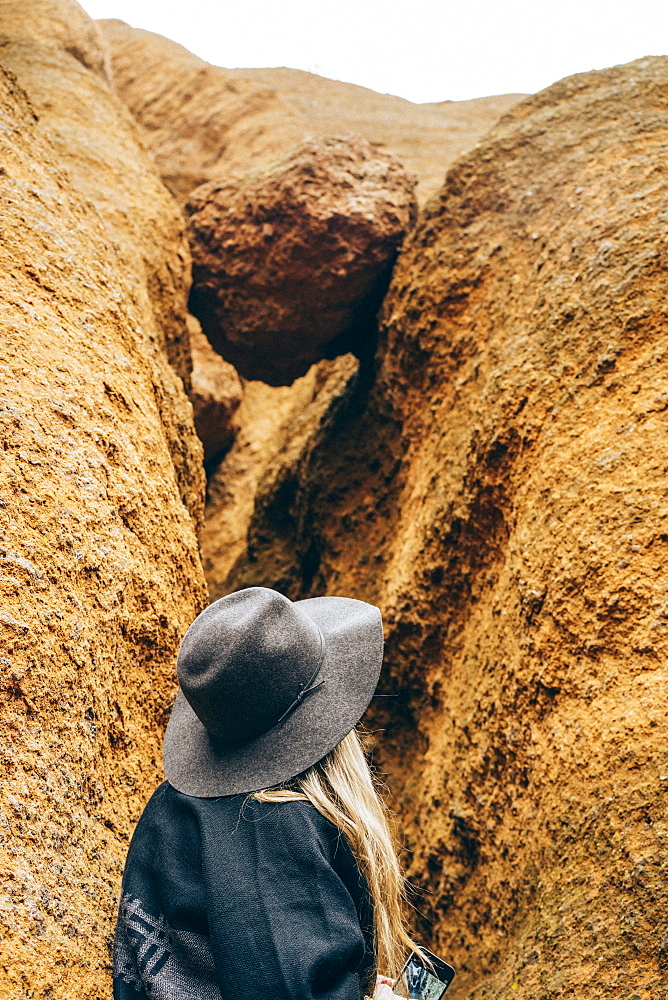 A woman explores a crevice in a rock, Eagles Rock, Red Mountain Trail, Arizona, United States of America
