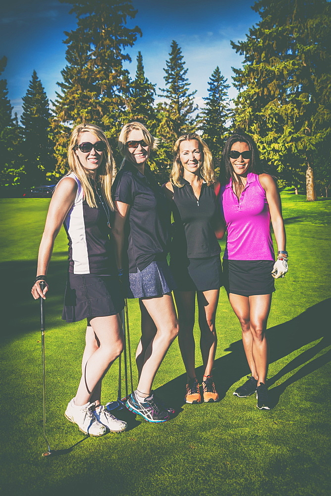 Four female golfers posing for a social media portrait on a golf course with a vintage style filter applied to the image, Edmonton, Alberta, Canada