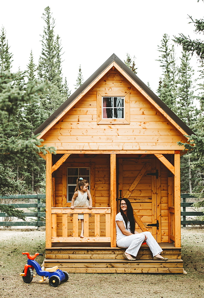 Mother and daughter with a wooden playhouse, Alberta, Canada
