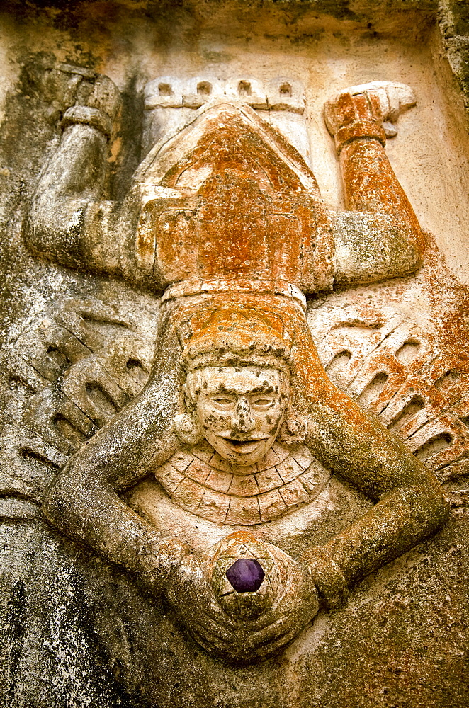 Close-up view of human figure splayed like a toad and holding a purple stone, carved on the side of a Mayan ruin, Tulum, Quintana Roo, Mexico - 1116-48257